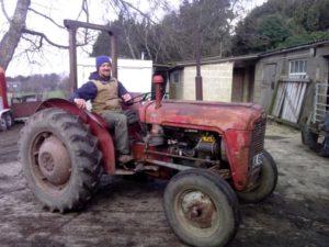 Farmer Sam sitting on a red tractor